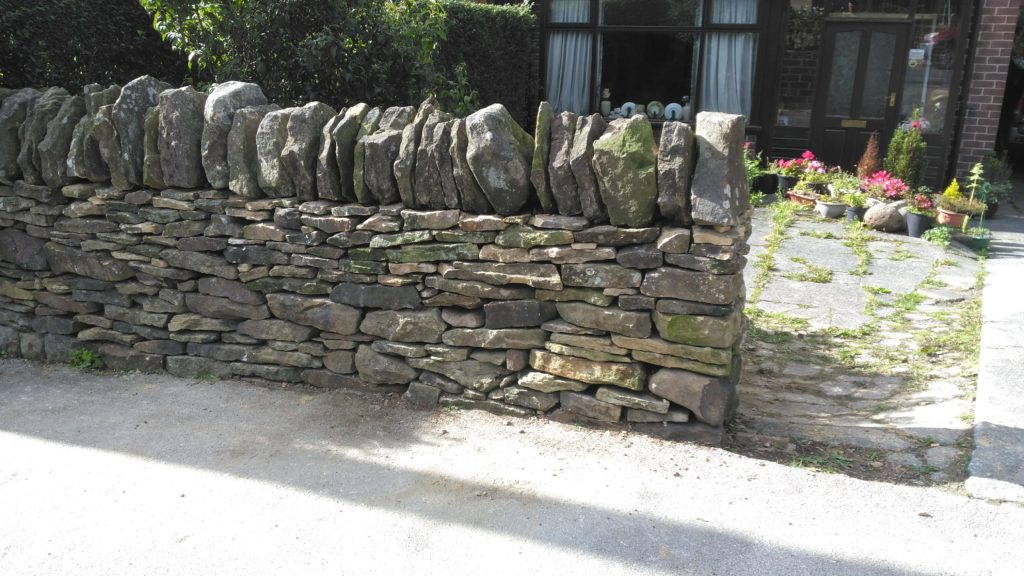 The finished  repair to a dry stone wall in middle of Longridge